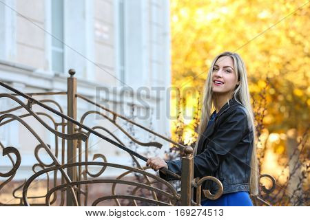 Beautiful young woman near vintage banister on bright autumn day