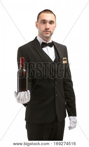 Young handsome waiter holding wine bottle on white background