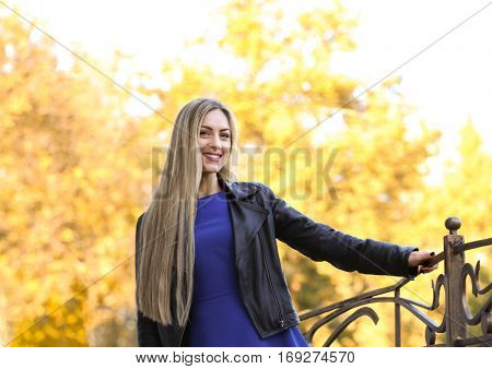 Beautiful young woman outdoors on bright autumn day
