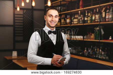 Young handsome waiter with notebook and pen standing in the restaurant