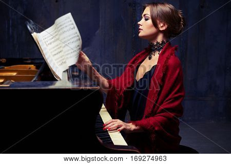 Side mid shot of delighted young woman who is turning the sheet music with notes while playing the piano