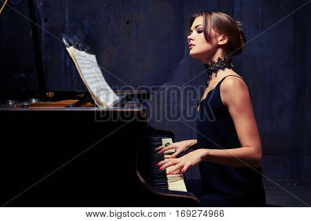 Side mid shot of exhilarated young Caucasian woman focusing on sheet music with notes while sitting down to the piano and playing