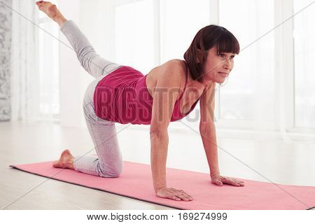 Close-up of sporty woman doing pilates workout on a mat in the gym. Fitness and healthy lifestyle concept. Doing balance exercise