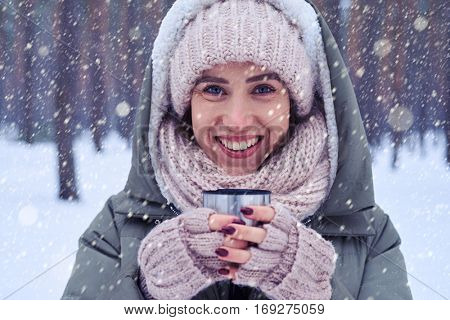Extreme close-up of female wearing warm winter clothes holding a cup with a drink. Young woman holding cup with tea outdoors in winter