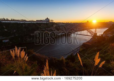 Panorama of the Douro river and Dom Luis I bridge during sunset, Porto, Portugal.