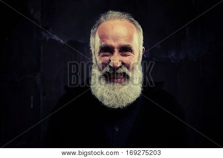 A mid shot of grey beard man standing against black background. Man doing grimace having joyful air