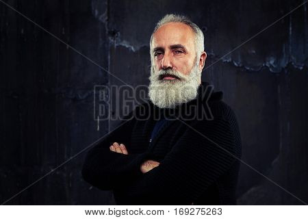 A mid shot of a man folding arms, standing against the black background, looking censoriously. Male having a serious look