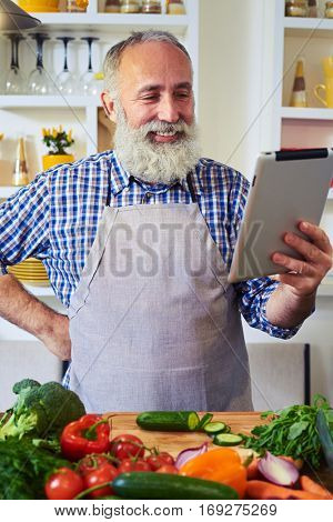 Close-up of cheerful man wearing gray apron using tablet to find a recipe. Looking at recipe on digital tablet. Having ingredients to prepare a healthy diet