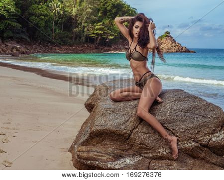Sensual brunette woman in gold and black bikini with beautiful hair sitting on the rock over beautiful sea and tropical island background