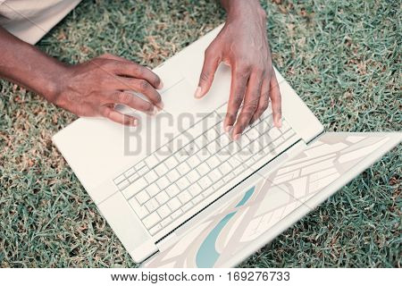 Digitally generated image of map against person using laptop on grass