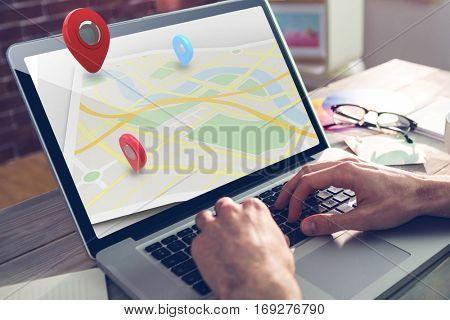 Map location marker against cropped hand of graphic designer using laptop