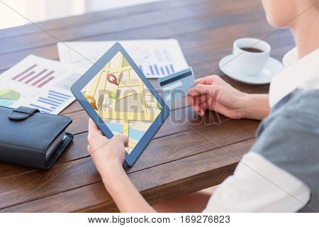 Map app against businesswoman using tablet pc and holding credit card