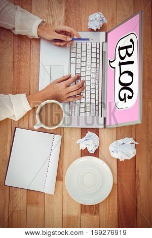 Bubble blog against cropped image of woman with pen using laptop
