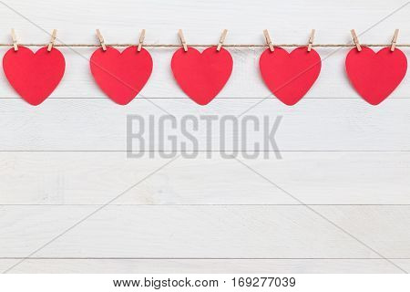 Red Paper Heart Hanging On Brown Nature Rope With Mini Clothespin. On White Wooden Plank. For Valent