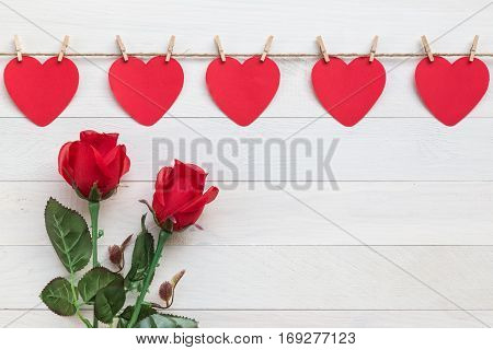 Red Paper Heart Hanging On Brown Nature Rope With Mini Clothespin And Rose Flower. On White Wooden P
