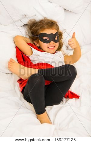 girl super hero with a mask is sitting on a white bedthe concept of leadershipvictory