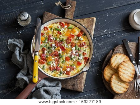 Vegetable frittata in a cast iron skillet on wooden background. Delicious brunch top view