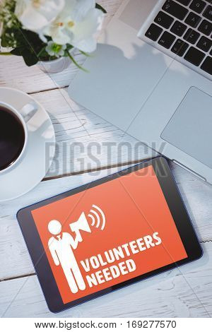 Volunteers needed against tablet and laptop on table