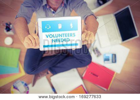 Beige volunteers needed against businessman showing tablet computer in creative office