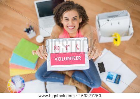 Grey volunteer against smiling businesswoman showing digital tablet in creative office