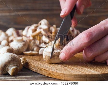 Woman hands slices mushrooms in kitchen. Female making mushroom sauce