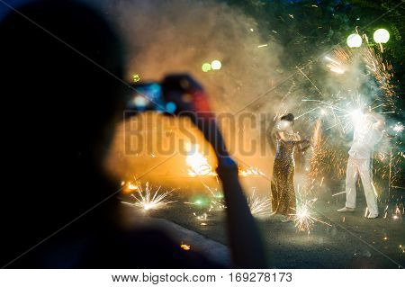 Fire Show In The Open Air In The Dark. Man And Woman Show Tricks With Fire