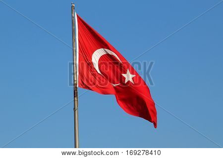 Turkey's national flag, red with crescent moon and star, on flagpole.