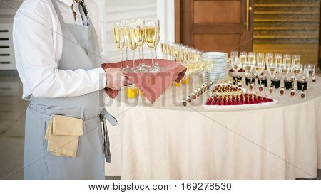Waiter With A Tray Of Champagne In Hand On Background Fourchette Table