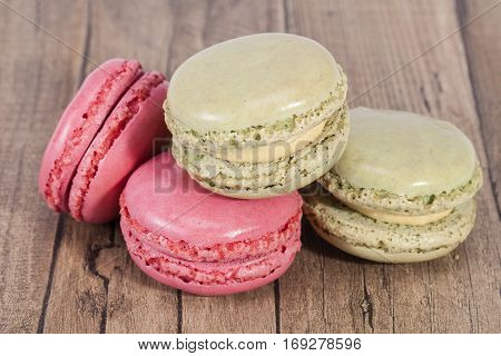 Colorful cookies of macaroon isolated on wooden plank.