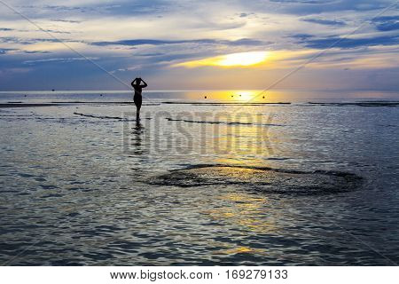 Women silhouette morning on Thung Wua Lan Beach at Chumphon Province Thailand.
