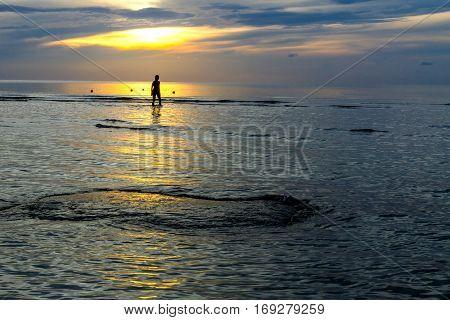 Women silhouette sunrise on Thung Wua Lan Beach at Chumphon Province Thailand.