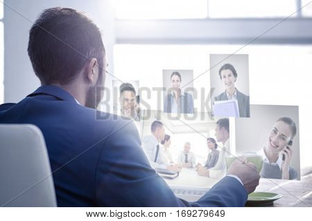 Business people having a meeting against business professional holding coffee cup while working on laptop