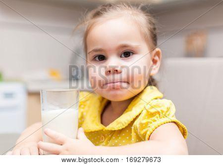 Child girl drinking milk at the kitchen