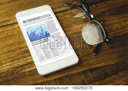 High angle view of cellphone and eyeglasses against business newspaper