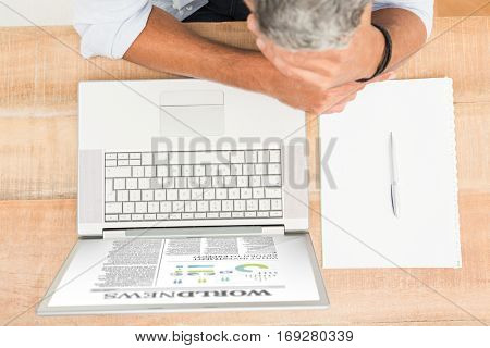 International newspaper against exhausted casual businessman leaning on wooden desk