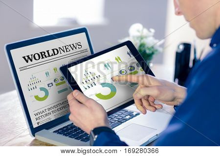 Businessman using tablet computer in office against international newspaper