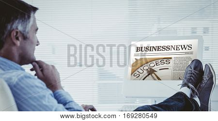 Relaxed man with feet on desk using computer against business newspaper