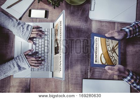 Close up on newspaper against overhead view of hands working at desk