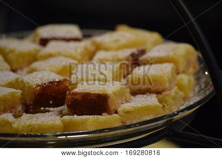 Lemon squares covered with powdered sugar on a serving tray.
