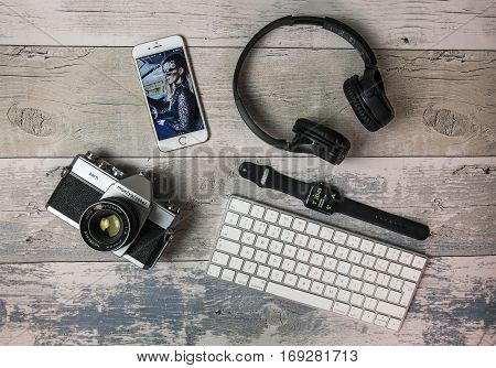 SWINDON UK - FEBRUARY 7 2017: Flat Lay with old SLR film camera iPhone Apple watch keyboard and headphones
