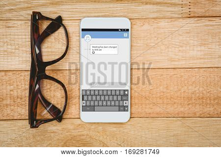Smartphone text messaging against view of glasses and a smartphone