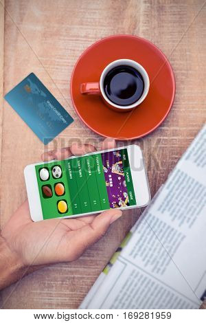 World credit card against overhead view of person using smart phone by coffee