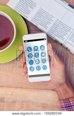Telephone apps icons against man using smart phone by coffee and newspaper on table