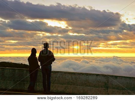 Silhouette couple looking at the beautiful sunrise on the top of mountain with the view into misty valley. Morning mountain landscape with wave of fog Doi Inthanon National Park Chiang Mai Thailand