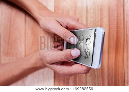 Telephone with apps icon against part of hands typing on smartphone