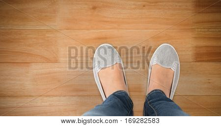 Casually dressed womans feet against wooden flooring