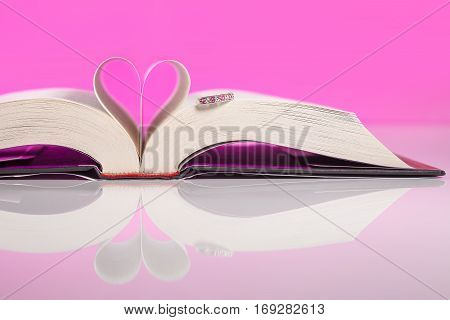Book of love isolated on pink background. Love inspired stories show that faith forgiveness and hope have the power to lift spirits and change lives always.