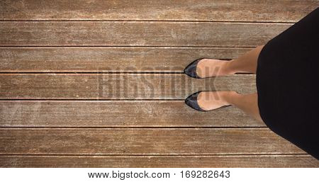 Businesswomans feet against wooden planks background