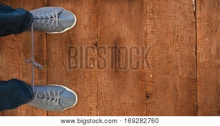 Man with shoelaces tied together against wooden planks
