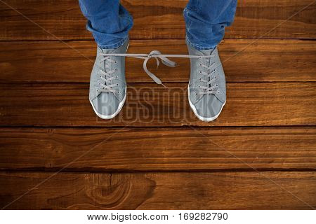 Low section of man with shoelaces tied together against overhead of wooden planks